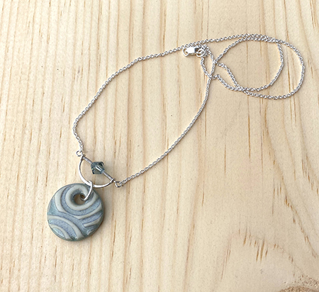 Swirly textured blue gray porcelain pendant with sterling silver half circle framing a matching crystal. The pendant is shown at an angle with chain gently coiled on a pine board background.